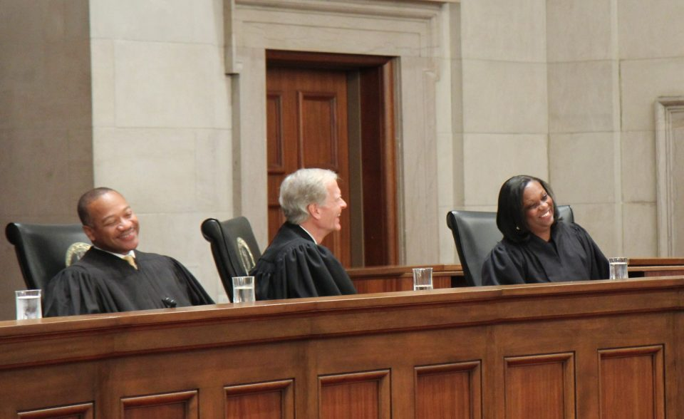 Justice Cleo E. Powell takes her seat on the beach after her investiture, October 21, 2011. To her left are Justice S. Bernard Goodwyn, far left, and Justice William C. Mims.